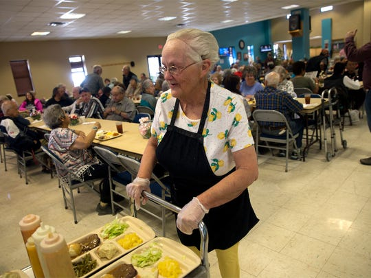 Kitchen aide Dian Terrell brings food to diners at the Bonnie Dallas Senior Center in Farmington.