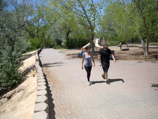 Vanessa Yazzie, left, and Aidan Lee take a walk Wednesday along the Animas River in Berg Park in Farmington.