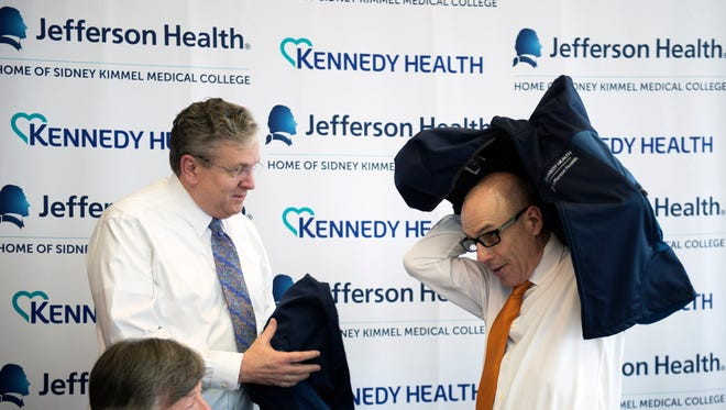 President & CEO of Kennedy Health Joseph Devine, left, and President & CEO of Thomas Jefferson University & Jefferson Health try on their new jackets Friday, Jan. 22 at Kennedy's Washington Township campus.
