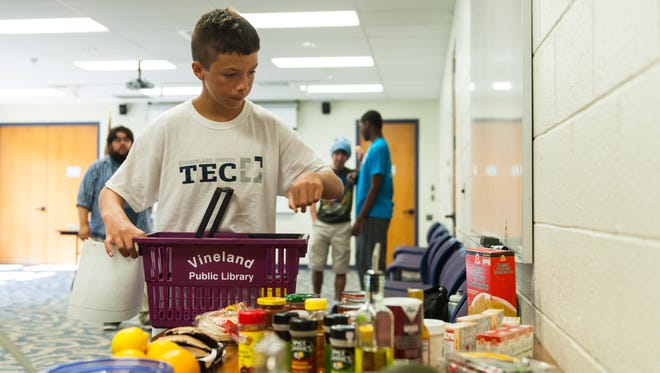 Logan Stahl picks his team's ingredients during the first ever Teen Iron Chef at the Vineland Library on Wednesday, August 3.