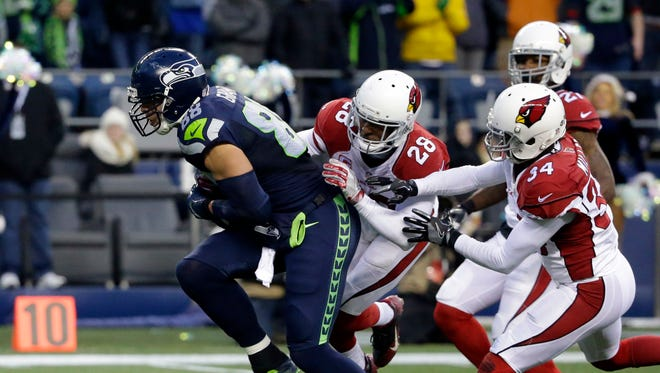 Seattle Seahawks' Jimmy Graham, left, breaks loose from Arizona Cardinals' Justin Bethel (28) and Harlan Miller (34) to score in the second half of an NFL football game, Saturday, Dec. 24, 2016, in Seattle.