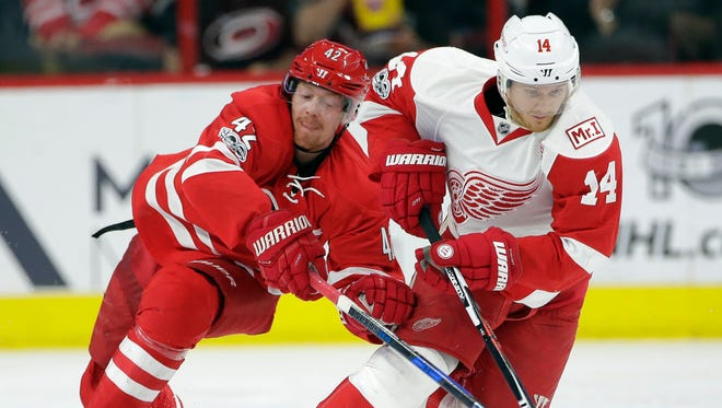 Red Wings forward Gustav Nyquist (14) and the Hurricanes' Joakim Nordstrom (42) chase the puck during the second period Tuesday in Raleigh, N.C.