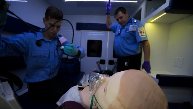 Paramedic students Frank Civitano, left, and Robert Leach work inside a mock ambulance during a simulation Thursday at Rowan College at Burlington County campus in Mount Laurel.