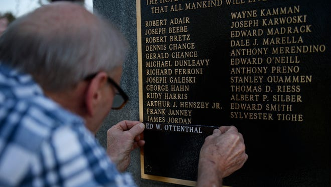Al Kohlmyer adds a nameplate for Ed W. Ottenthal at a Vietnam War memorial monument Friday, April 13, 2018 in Berlin, N.J.