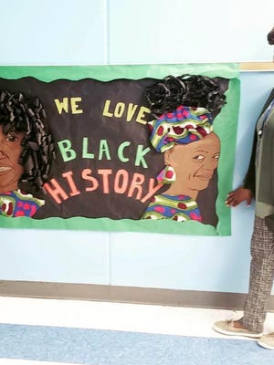 Margie Kidd stands in front of bulletin board that was made last year for her and fellow teacher Patricia Moye by coworker Courtney Simmons. Kidd, who loved African American history, died Sept. 28 of COVID-19 complications.