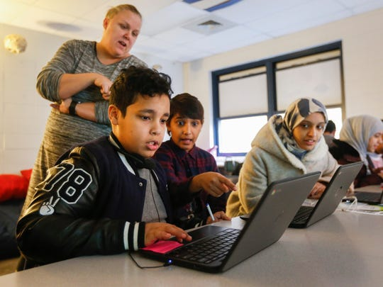 Zeyad Sulaimani, center, points at Ghazi Al Harbi's computer screen during a quiz game in Jan McClellan's class at Carver Middle School on Wednesday, Feb. 21, 2018.