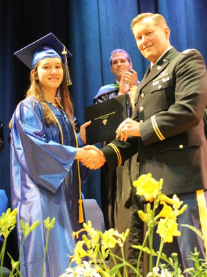 Esther Roman receives a certificate of admission from James P. Trainor of the U.S. Military Academy at West Point during the June 3 event.