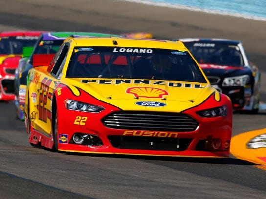 Joey Logano leads a pack of cars on his way to a victory