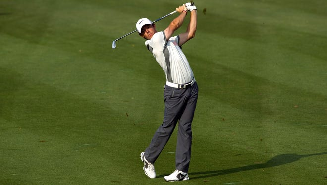 Rory McIlroy of Northern Ireland takes a shot on the 15th fairway during the second round of the 2014 Omega Dubai Desert Classic in Dubai. McIlroy leads the tournament after two rounds.