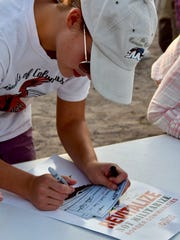 Caitlin Miller signs messages of protest to elected