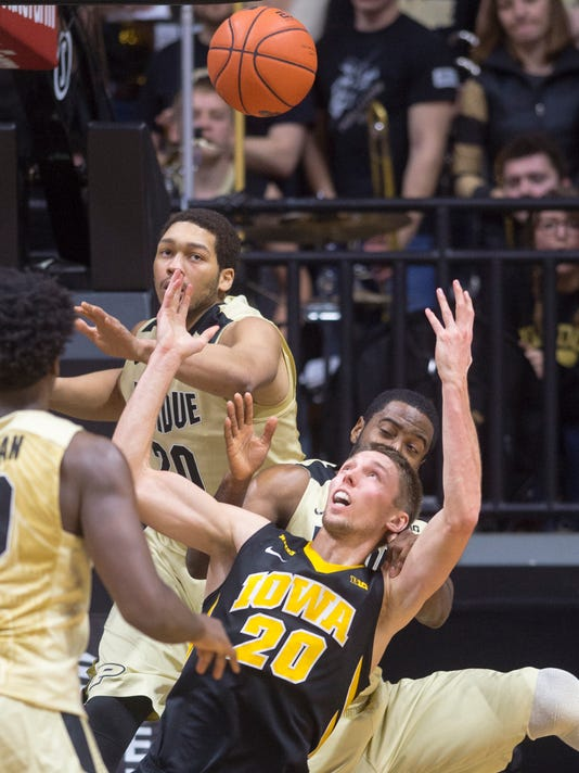 Iowa forward Jarrod Uthoff (20) tries to regain control of the ball as he is fouled by Purdue guard Rapheal Davis,rear, during the second half of an NCAA college basketball game, Jan. 2, 2016, in West Lafayette, Ind. Iowa won 70-63. (AP Photo/Doug McSchooler)