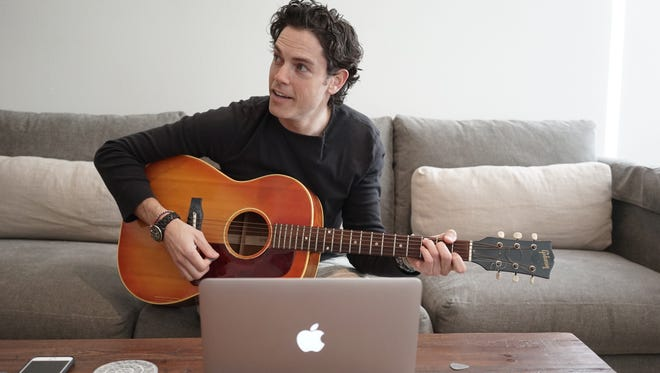 Stageit founder Evan Lowenstein in his living room, putting on a concert to fans.