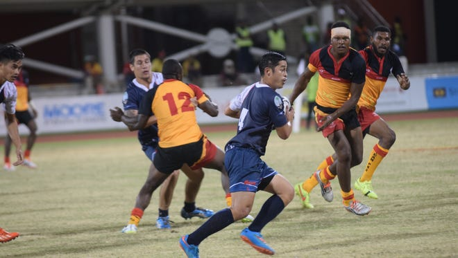 Guam national rugby player Eddie Calvo looks for an opening during their game against the Papua New Guinea national team July 8 at the 2015 Pacific Games in Port Moresby, Papua New Guinea. Team Guam fell 53-0 in its second match of the day at the Sir John Guise Stadium