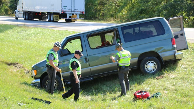 Three people were injured when this van rolled over on U.S. 30 Sunday, trapping a Bucyrus man underneath.