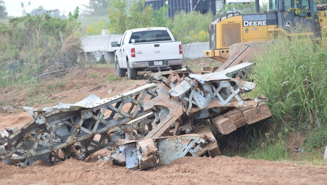 A piece of the O.K. Allen Bridge superstructure sits along the bank of the Red River on Tuesday. Work to remove pieces of the demolished bridge from the river is continuing.