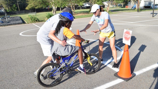 Stacey McMickens (right) of Fit Families for Cenla teaches Chelsea Ugokwe (left), a third-grader at Our Lady of Prompt Succor, how to brake in an emergency during a bike clinic conducted at the school Wednesday.