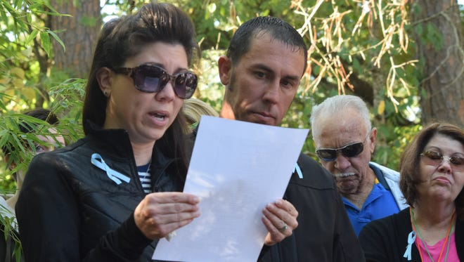 Amy Barton (left), with husband Justin Barton by her side, reads a poem at Healing Hearts' annual Walk to Remember held Saturday at the Alexandria Zoo. The Bartons were there, along with their family, to remember their late son Nathan Thomas Barton who would have been 8 years old. Amy said Nathan was lost at 34 weeks and was stillborn.
