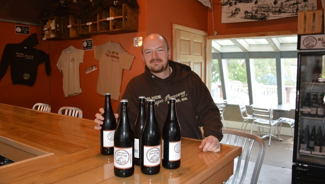 Nick Calaway, head brewer at Ahnapee Brewery, with the 16-ounce hand-bottled beer currently sold at its Algoma tap room.  The beer will be available  next spring in 12-ounce bottles in Northeast Wisconsin stores.