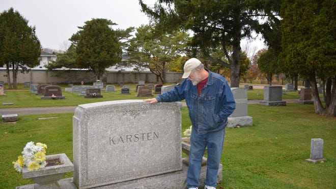 Historical Society President Tom Schuller stands beside the grave of Great Lakes sea captain Bill Karsten, whose ghost was often seen in the Hotel Karsten.