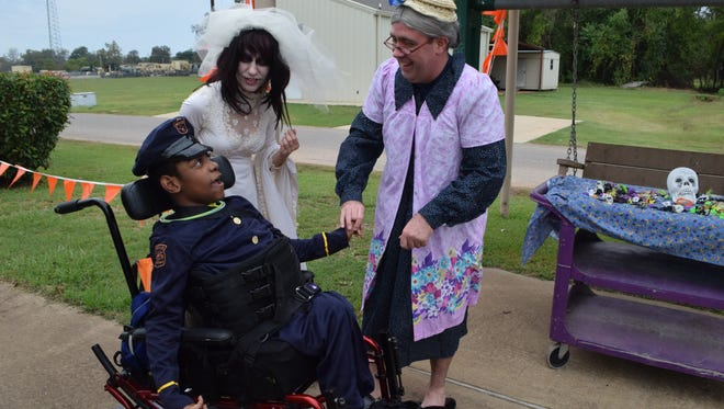 Johntavius (left), a student at the Louisiana Special Education Center, looks at the school's social worker, Mark Byrd (right) who is dressed as a grandmother. Ann Sehon (center), a teacher at the school, is dressed as a Day of the Dead bride. The school's students and personnel dressed up and participated in a schoolwide trick or treating celebration at Pelican Park. All departments gave out goodies to the students.