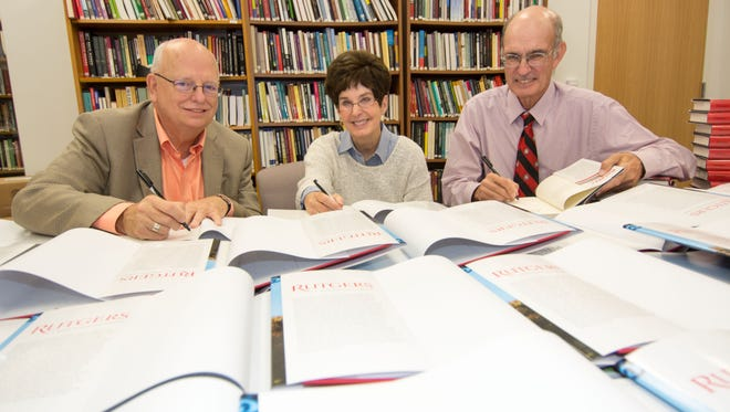 Two contributors to Rutgers: A 250 Anniversary Portrait, Barry Qualls, left, professor of English and former vice president of undergraduate education, and Linda Stamato, co-director of the Center for Negotiation and Conflict Resolutions and former chair of the Rutgers Board of Governors, joinRutgers Since 1945 author Paul G.E. Clemens during a book signing.