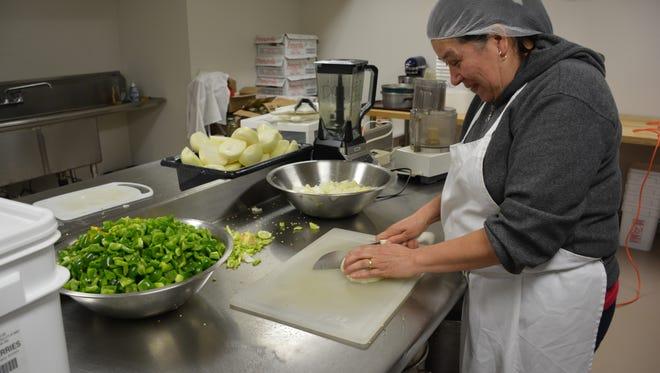 Maria Brajs of Kewaunee helps prepare the ingredients for Door County Wildwood Market cherry salsa at the Algoma Farm Market Kitchen.