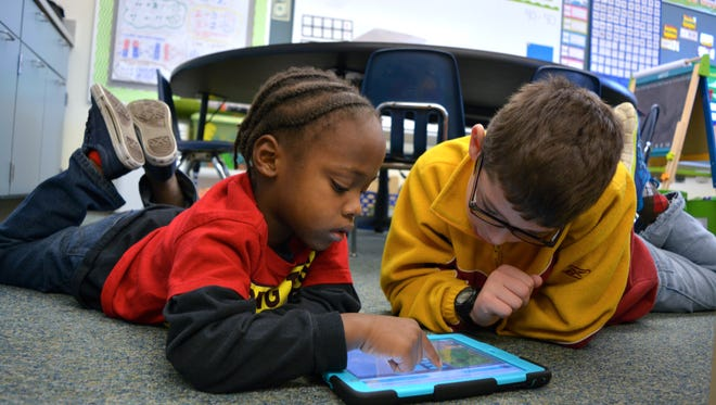 Kindergartner Sunder Copes and fourth grader Austin Wiswall work on a programming lesson at Richard A, Shields Elementary School Wednesday, Dec. 9.