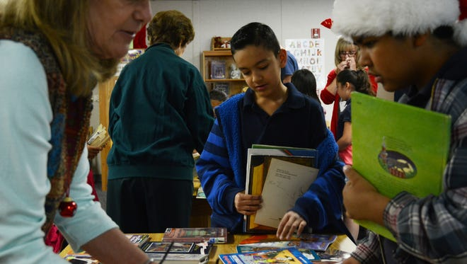 Palm View Elementary fourth grader Hector Varela (center) contemplates which books he wants to take home. Read With Me volunteers donated nearly 6,000 books to students at Palm View as a Christmas present.