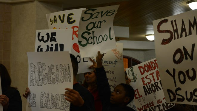 Supporters at John Adams Elementary School held up signs at Tuesday's board meeting in Desert Sands Unified School District to oppose the proposal to close the school.