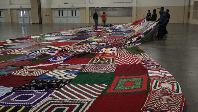 Staffers from Caron in Washington, N.C., layout the world's largest Christmas stocking, made with Caron United yarn.