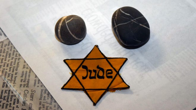 """Rabbi Arnold Task, who was the rabbi at Congregation Gemiluth Chassodim for 22 years, brought artifacts to a talk he gave about the Holocaust on Tuesday. The two rocks he got on a visit to Dachau concentration camp. The yellow Star of David patch was given to him by Otto Loeb of North Carolina who was imprisoned at Dachau. """"Jude"""" means """"Jew."""""""