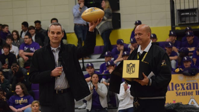 Chris Boniol (left), former kicker for the Dallas Cowboys and 1990 Alexandria Senior High School alum, holds up a gold football given to Alexandria Senior High School from the NFL as ASH principal Duane Urbina holds the box it came in. The NFL is honoring high schools who've had alumni play in the Super Bowl with gold football. The event is being done in celebration of the 50th anniversary of the Super Bowl.