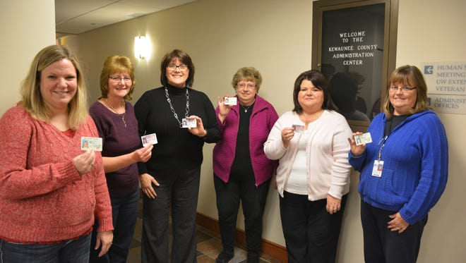 Kewaunee County employees display their driver's license or other  government-issued photo IDs to remind voters to bring them to vote in Tuesday's primary.  Left to right:  Jamie Annoye, county clerk; Bonnie Purzner, deputy treasurer and clerk of West Kewaunee; Michelle Dax, treasurer; Janet Wolf, register of deeds; Germaine Bertrand, deputy register of deeds; and Sandy Pelishek, land information assistant.