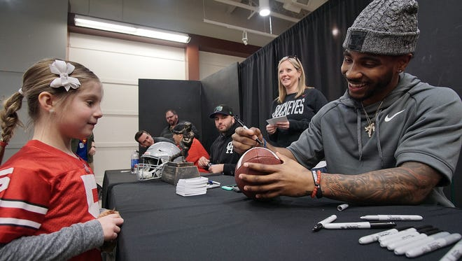 Aubrey Dilger, 8, of Norwalk gets her football signed by former Ohio State star Braxton Miller during his appearance at the Richland Mall on Saturday.