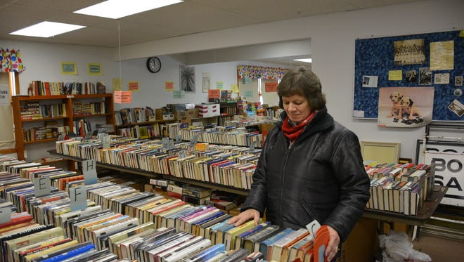 Mary Wolske, a member of the Friends of the Library, sorts some of the group's donated books.   The group is seeking a new location for its book sales that benefit the Kewaunee Public Library..