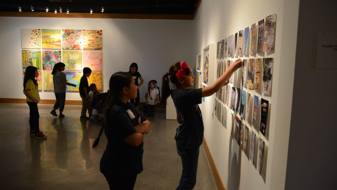 Two students from Abraham Lincoln Elementary School try to match photo cards to the abstract paintings on the wall at the Marks Art Center at College of the Desert.