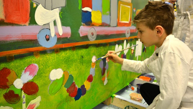 Buckingham Elementary School third grader Luke Clark paints on a mural that will soon be on display in downtown Berlin. Phase one of the mural will be unveiled at the Berlin Arts Stroll on March 11, 2016.