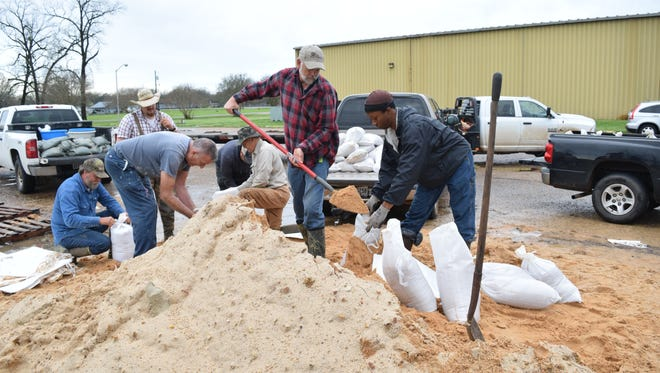 Bryan Bunting (front, left) helps Quentin Sergent fill sandbags in the parking lot of the Grant Parish Civic Center in Colfax Friday.