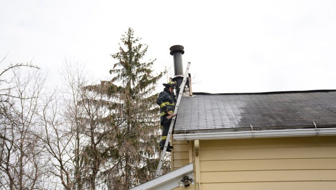 A firefighter on the roof near the chimney of a home that caught fire Sunday resulting to damage in its attic Nobody was injured.