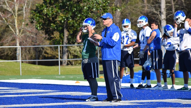 UWF coach Pete Shinnick confers with quarterback Kaleb Nobles during spring practice on Argos AstroTurf Field, which is now Pen-Air Field after a $1 million gift for naming rights by Pen-Air Federal Credit Union.