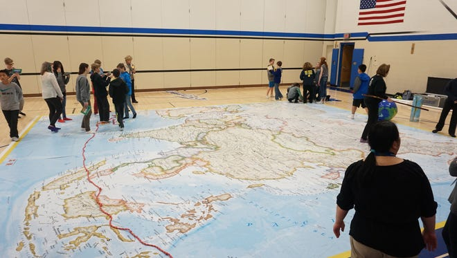 Interactive educational activities help John Muir students explore a giant map of Asia.
