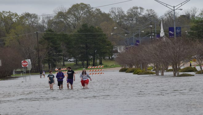 Northwestern State University students Shelby Riedel (left), Blake Blanchard, Nicholas Jones and Jessica Trahan cross the intersection of Highway 1 and Highway 6  in Natchitoches March 10. The intersection was closed due to flooding.