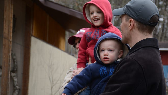 1-year-old Thomas Fisher, bottom, his father Jared Fisher, 34, and his older brother Derek Fisher, 3, check out the Binghamton Zoo at Ross Park's new fishing cats Sunday at the second day of the zoo's first event of the season: Eggstravaganza.