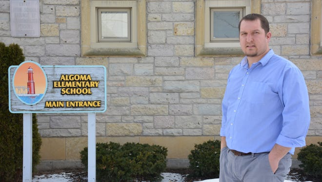 Algoma Superintendent. Nick Cochart stands in front of sign for the elementary school's current entrance, which will be redesigned for better access and security.   A new canopied entrance for the theater/performing arts center will be located on Fremont St. and separated from the rest of the school.
