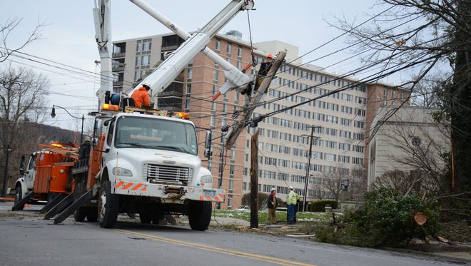 NYSEG authorities repair a power line down in downtown Binghamton after a tree fell on it Sunday.