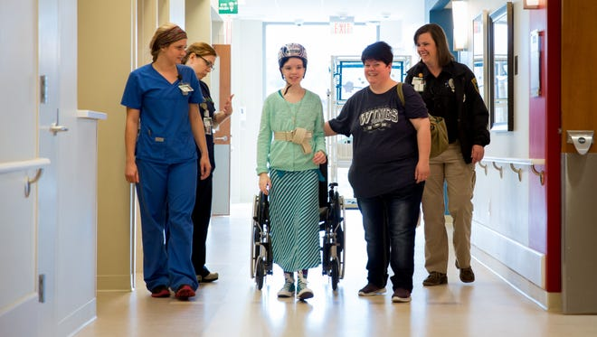 Shooting survivor Abigail Kopf walks through Mary Free Bed Rehabilitation Hospital in Grand Rapids with medical professionals and her mother, Vicki.