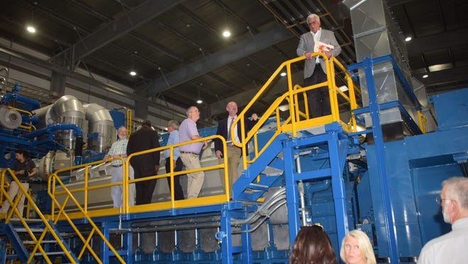 """Tom David Jr. (top, far right) of Pan American Engineers gives a tour of the new generators at the Alexandria power plant on Friday. David, a consultant on the generator project, said, """"Today, this is the fastest-starting plant in America."""""""