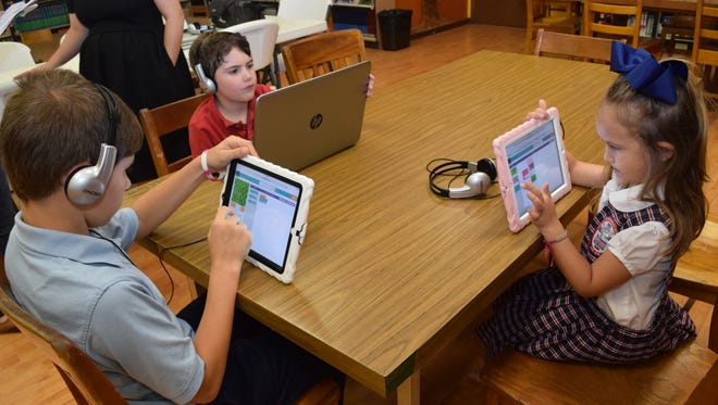 St. Frances Cabrini School students Christopher Waits (left), Conner Jeanise and Riley Lemoine learn the basics of coding Friday. The school will offer a coding curriculum next year.