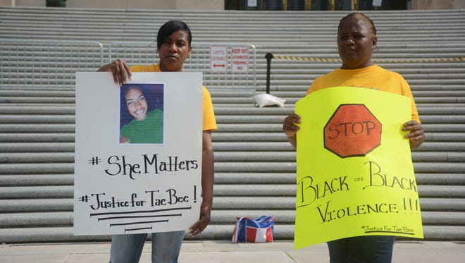 Theresa Tillman (left), and Lydia Larce hold signs at the Capitol Thursday urging for justice for the two 19-year-old Southern University students who were slain in April near LSU.