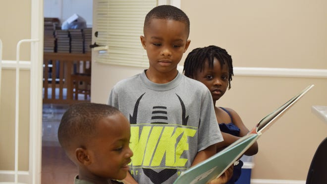 From left, Mason Mister, 3, Isaiah Mister, 7, and Olivia Mister, 4, all of Petal, look at a book after story time at Petal Library.